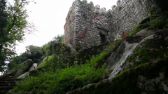 Tourists walk into Castle of the Moors fortress wall, tilt up, Sintra, Portugal Stock Footage