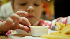 Little kid girl closeup eating french fries with sauce in a fast food restaurant Stock Footage