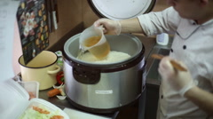 The chef pours vinegar mixture into the rice Stock Footage