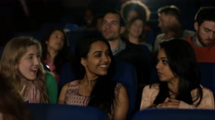 4K Happy young female friends watching a film with 3D glasses in movie theatre - stock footage