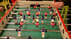 Playing game of table soccer fast spinning tubes Stock Footage
