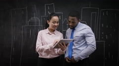 4KBusinessman & woman standing in front of blackboard with drawings of buildings - stock footage