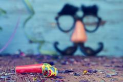 party horns, confetti and fake glasses, nose and mustache - stock photo