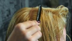 Stock Video Footage of Hairdresser separates hair of the blonde