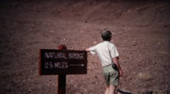 1972: Man pointing to natural bridge attraction half mile away from sign. Stock Footage