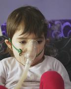 girl making inhalation with mask on her face - stock photo