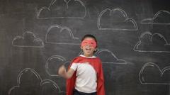 4K Little boy superhero in front of blackboard with drawings of buildings Stock Footage