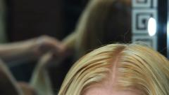 Combing and curling hair strand of the blonde - stock footage