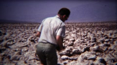 1972: Man tasting ground salt in dried up desert lake bed. Stock Footage