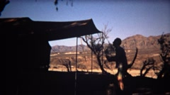 1972: Man setting up camping tent silhouette with beautiful mountain background. Stock Footage