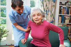Stock Photo of Carer Helping Senior Woman Out Of Chair