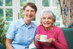 Senior Woman At Home With Carer - stock photo