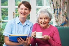 Senior Woman With Carer At Home - stock photo