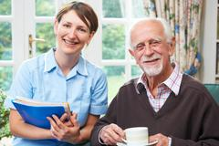 Senior Man With Carer At Home - stock photo