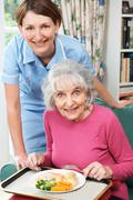 Carer Serving Lunch To Senior Woman Stock Photos