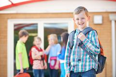Boy Standing Outside School Classroom With Rucksack - stock photo