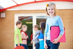 Girl Standing Outside School With Book Bag - stock photo