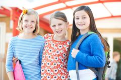 Group Of Girls Standing Outside School With Book Bags Stock Photos