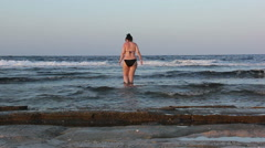 Woman enters the sea in the evening Red Sea Stock Footage