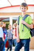 Boy Standing Outside School With Rucksack Stock Photos