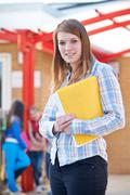 Portrait Of Teacher Standing In Playground With Folder - stock photo