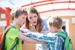 Teacher Stopping Two Boys Fighting In Playground Stock Photos