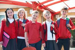 Portrait Of Schoolchildren Outside Classroom Carrying Bags Stock Photos