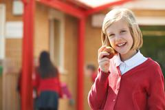 Female Pupil Eating Apple At Breaktime Stock Photos