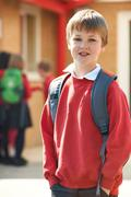 Boy Wearing Uniform Standing In School Playground - stock photo