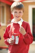 Boy In School Uniform Eating Potato Chip In Playground Stock Photos