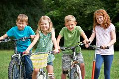 Stock Photo of Group Of Children Playing On Bikes And Scooter