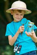 Boy Studying Butterfly Caught In Jar - stock photo