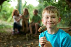 Boy Eating Sausage Around Camp With Friends Stock Photos