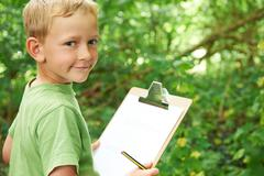 Boy Making Notes On School Nature Field Trip Stock Photos