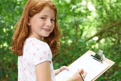 Girl Making Notes On School Nature Field Trip - stock photo