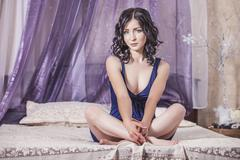 Woman beautiful brunette sitting on the bed with a canopy in the morning Stock Photos