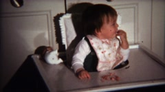 1971: Baby eating small food pieces from high chair tray. Stock Footage