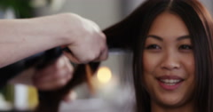An attractive young woman having her hair blow-dryed. Shot on RED Epic. Stock Footage