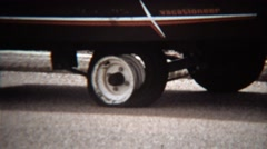 1971: Man fixing flat tire on camping trailer vacationeer vehicle. Stock Footage