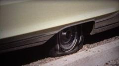 1971: Man fixes flat tire on white sedan car in hot sun. Stock Footage