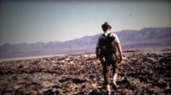 1971: Man walking across mountainous dry lake bed with backpack. Stock Footage