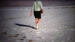 1971: Women walking on white salty dry lake bed in flat shoes. - stock footage