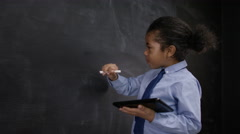 4K Cute little boy with tablet computer writing math sum on blackboard Stock Footage