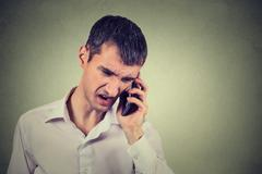 Angry business man screaming on the mobile phone - stock photo