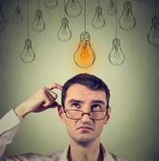 Stock Photo of Portrait thinking man in glasses looking up with light idea bulb above head .