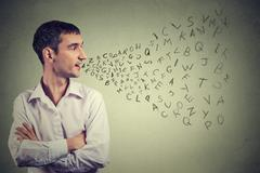 Side profile man talking with alphabet letters coming out of his mouth. Commu Stock Photos
