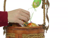 female hand putting easter eggs in the basket - stock footage