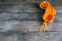Cut pumpkin on the wooden rustic table - stock photo