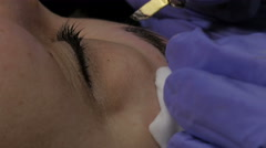 Beautician using tweezer and brush for eyebrow shaping, extreme close up. Stock Footage
