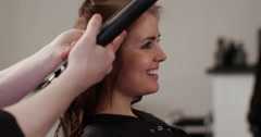 Young woman having her hair straightened while at the salon. Shot on RED Epic. Stock Footage